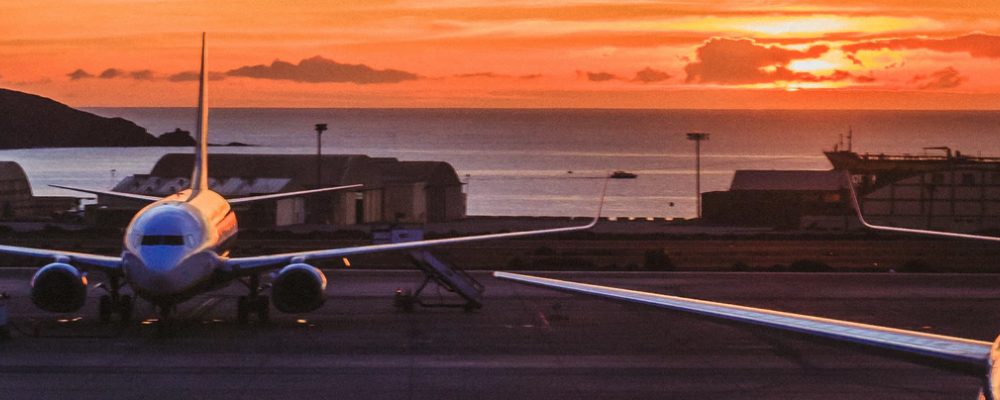 A Parked Airplane With A Sunset Above The Sea At The Background